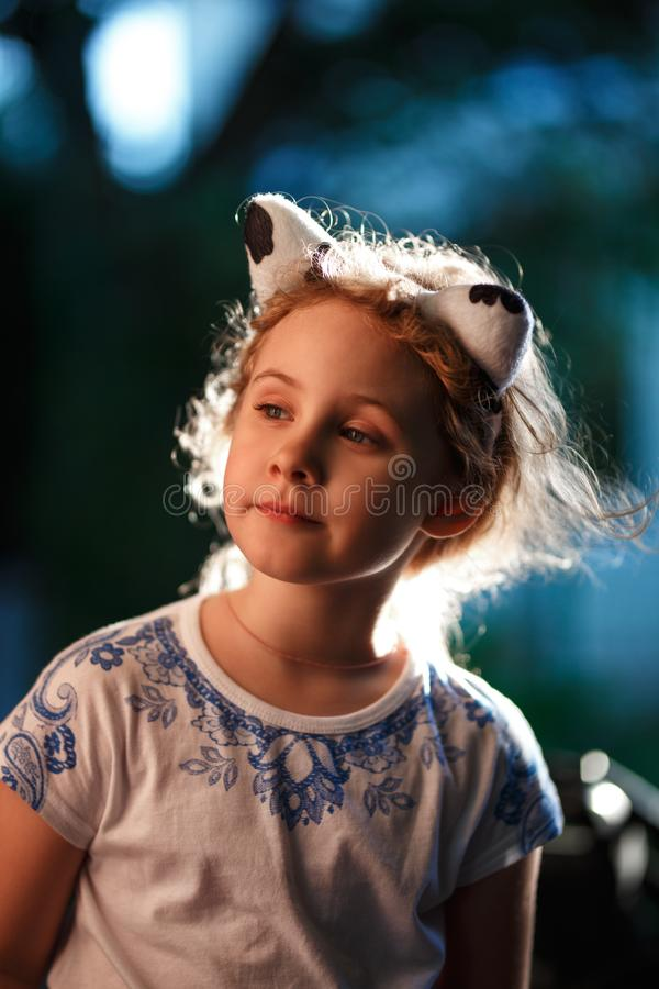 El retrato de un exterior de pelo rubio encantador de la situación de la muchacha en una tarde caliente del verano, el sol ilumin fotos de archivo