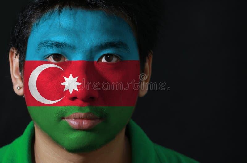 El retrato de un hombre con la bandera de la Azerbaijan pintó en su cara en fondo negro imágenes de archivo libres de regalías