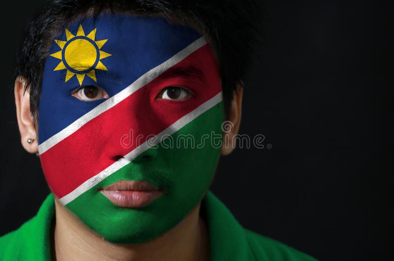 El retrato de un hombre con la bandera de la Namibia pintó en su cara en fondo negro foto de archivo