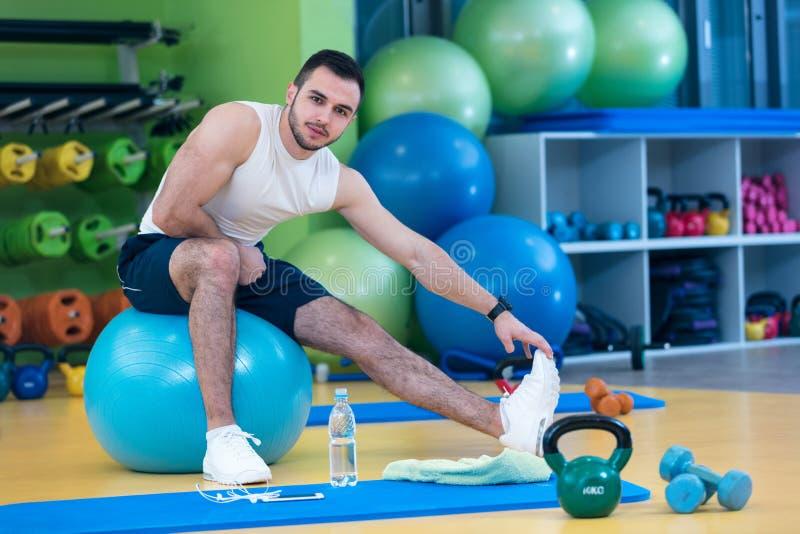 El retrato de un hombre de la aptitud que hace estirar ejercita en el gimnasio imágenes de archivo libres de regalías