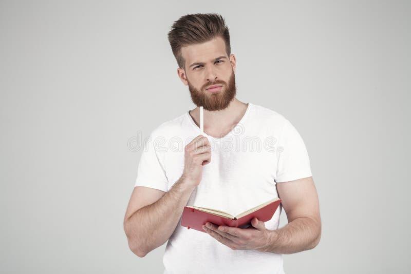 El retrato de un hombre hermoso con una barba y un peinado de moda vestidos en ropa informal se coloca cuidadosamente con una lib fotografía de archivo