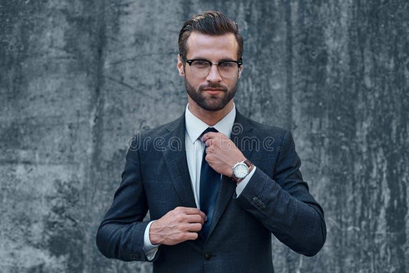 El retrato de un hombre de negocios hermoso sonriente con los brazos se plegó imagenes de archivo