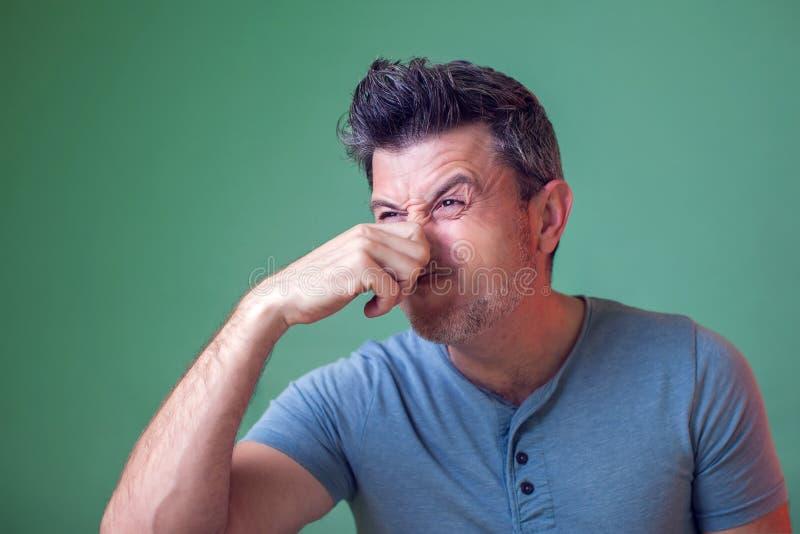 El retrato de un hombre se cierra la nariz, huele malo Gente, emociones, forma de vida fotos de archivo libres de regalías