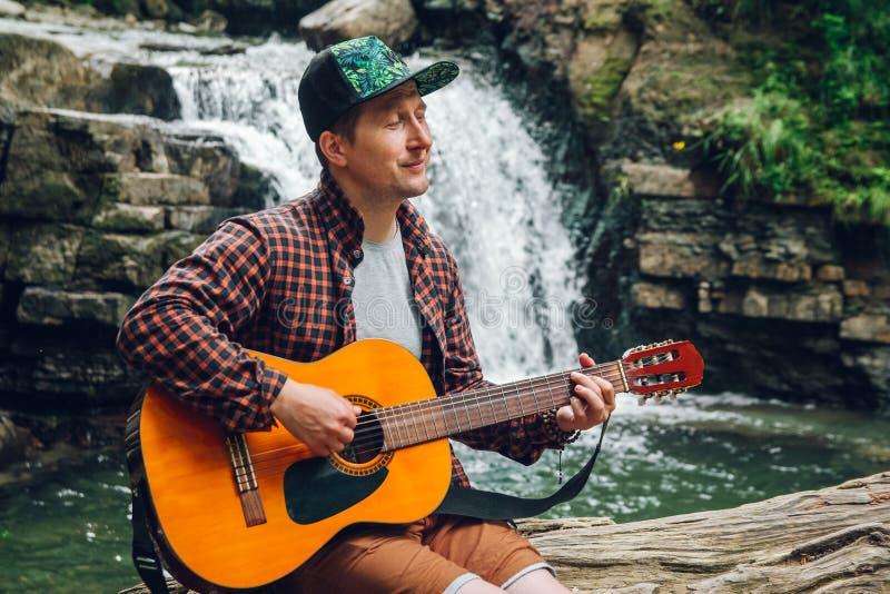 El retrato de un hombre toca una guitarra que se sienta en un tronco de un árbol contra una cascada Espacio para su mensaje de te foto de archivo libre de regalías