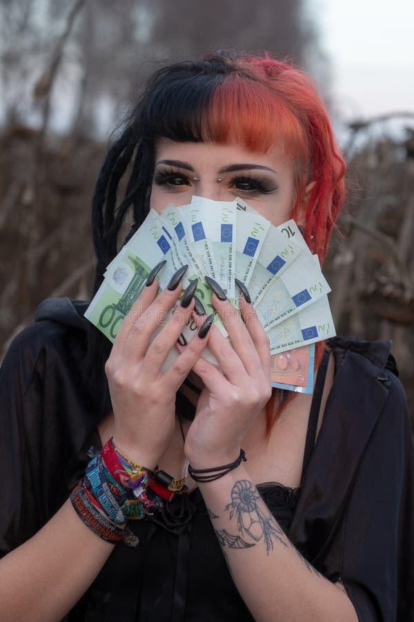 El retrato de un individuo joven hermoso, mujer excéntrica, está disfrutando de muchas cuentas euro fotos de archivo libres de regalías