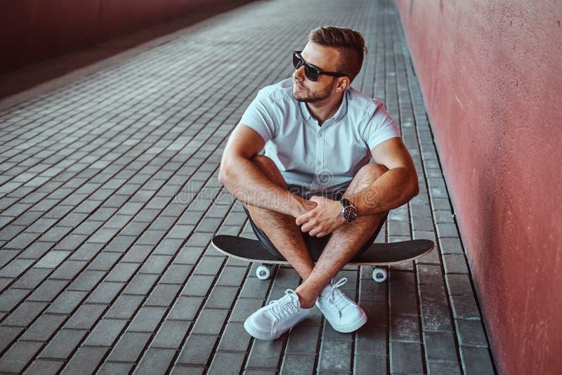El retrato de un individuo de moda hermoso del patinador en gafas de sol se vistió en una camisa blanca y los pantalones cortos q imágenes de archivo libres de regalías