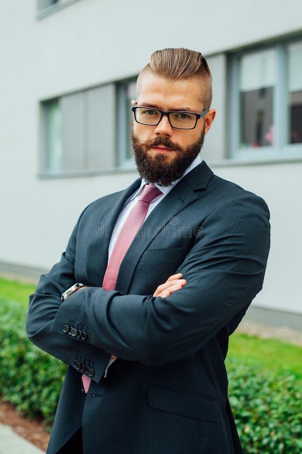 El retrato de un joven enfocó al hombre de negocios barbudo fuera del offi imagen de archivo libre de regalías