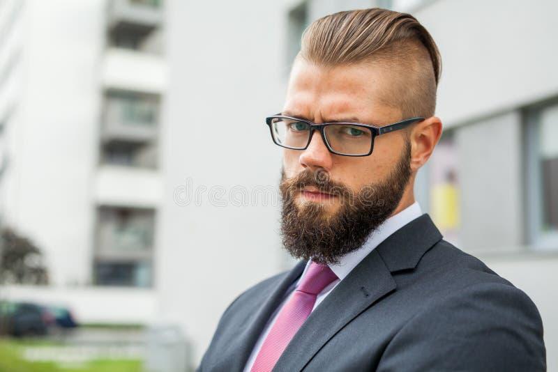 El retrato de un joven enfocó al hombre de negocios barbudo fuera del offi fotografía de archivo