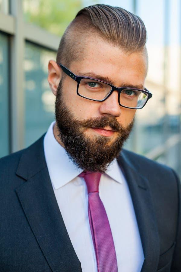 El retrato de un joven enfocó al hombre de negocios barbudo fuera del offi imágenes de archivo libres de regalías
