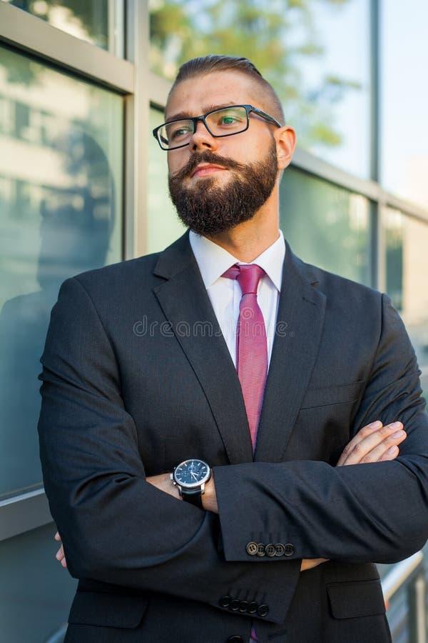 El retrato de un joven enfocó al hombre de negocios barbudo fuera del offi fotos de archivo libres de regalías