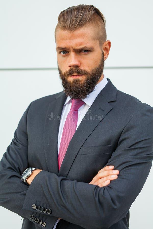 El retrato de un joven enfocó al hombre de negocios fuera de la estructura de la oficina foto de archivo