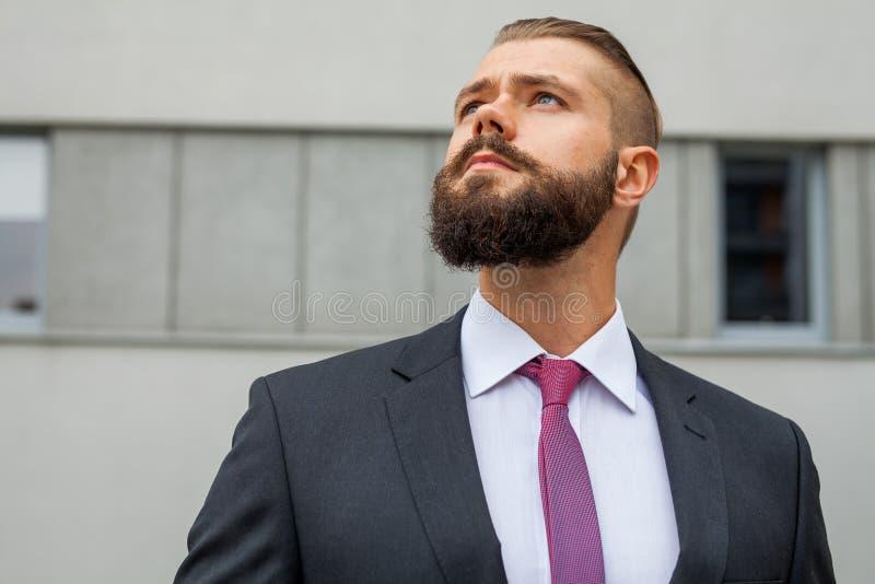 El retrato de un joven enfocó al hombre de negocios fuera de la estructura de la oficina imágenes de archivo libres de regalías