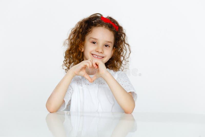 El retrato de un ligirl sonriente en las camisetas blancas que muestran forma del corazón con entrega el fondo blanco Copie el es foto de archivo