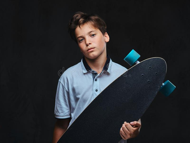 El retrato de un muchacho joven del patinador vistió en controles de una camiseta del blanco un longboard Aislado en el fondo osc imagen de archivo