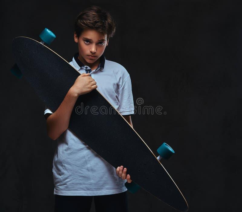 El retrato de un muchacho joven triste del patinador vistió en controles de una camiseta del blanco un longboard En el fondo oscu fotografía de archivo libre de regalías