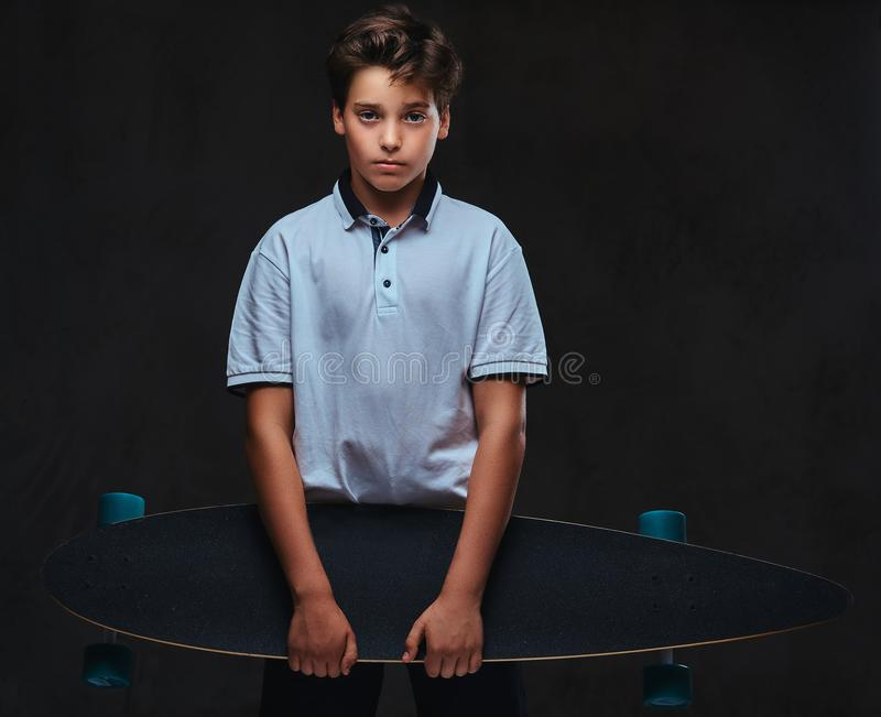 El retrato de un muchacho joven triste del patinador vistió en controles de una camiseta del blanco un longboard En el fondo oscu fotos de archivo libres de regalías