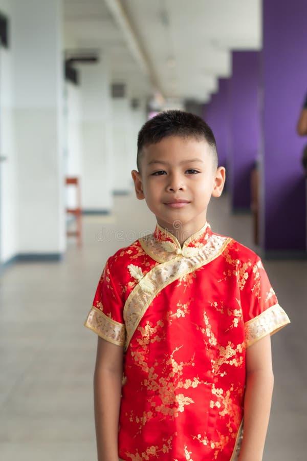 El retrato de un muchacho se vistió en China roja imagenes de archivo