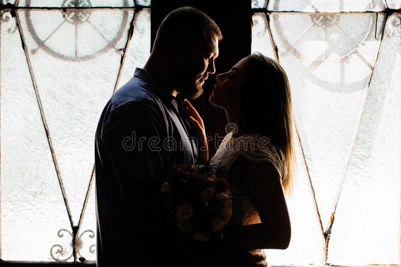 El retrato de un par romántico en un contraluz de una ventana o hace imagen de archivo