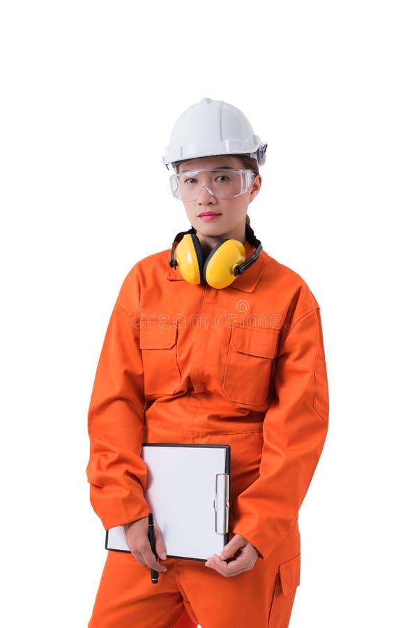 El retrato de un trabajador de mujer en el mecánico Jumpsuit está sosteniendo el tablero y la pluma aislados en el fondo blanco fotos de archivo