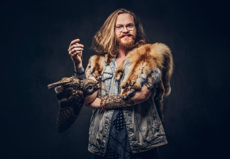 El retrato de un varón tattoed del inconformista del pelirrojo con el pelo lujuriante largo y la barba llena se vistió en una cam fotografía de archivo