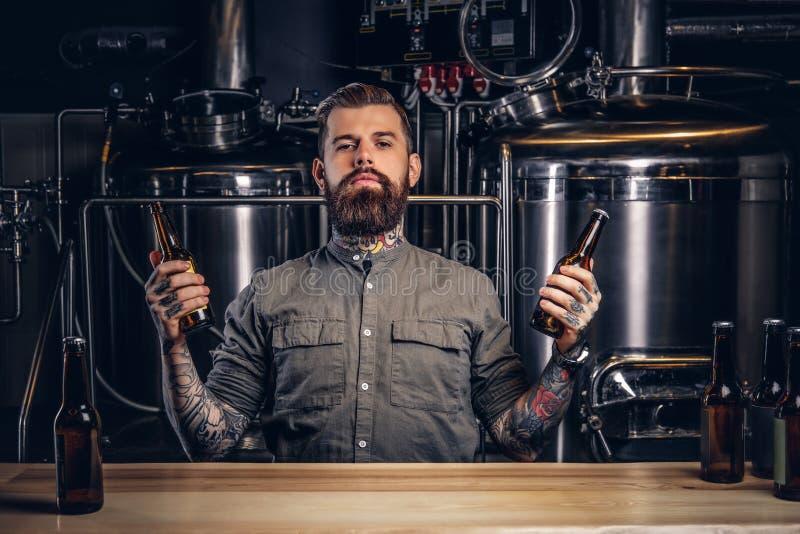 El retrato de un varón tatuado pensativo del inconformista con la barba elegante y el pelo sostienen dos botellas con la cerveza  foto de archivo