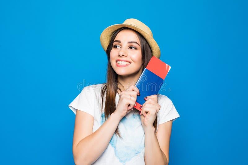 El retrato de un viajero lindo alegre de la muchacha en verano viste mostrar el pasaporte con los boletos a la cámara aislada sob fotografía de archivo
