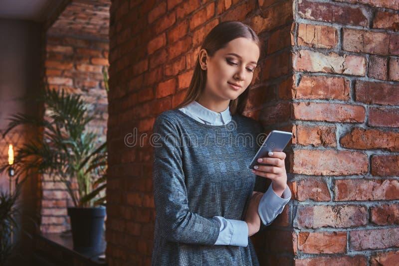 El retrato de una chica joven se vistió en un vestido gris elegante que se inclinaba contra la pared de ladrillo, usando smartpho imagen de archivo libre de regalías