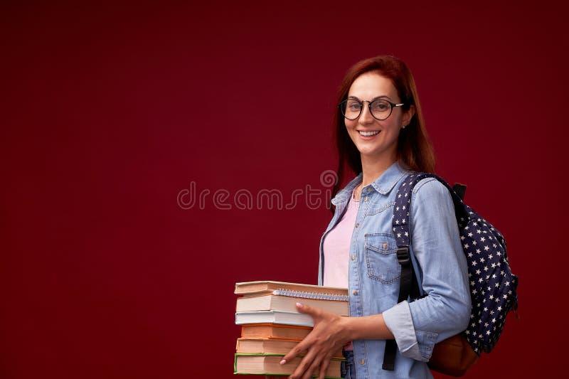 El retrato de una estudiante hermosa con una mochila y de una pila de libros en sus manos está sonriendo en el fondo rojo fotografía de archivo