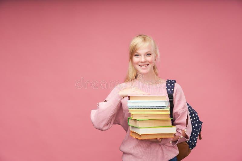 El retrato de una estudiante hermosa con una mochila y de una pila de libros en sus manos está sonriendo en el fondo rosado imagenes de archivo