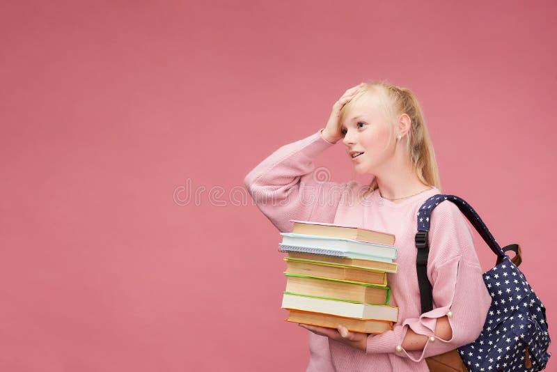 El retrato de una estudiante hermosa con una mochila y de una pila de libros en sus manos está sonriendo en el fondo rosado foto de archivo libre de regalías