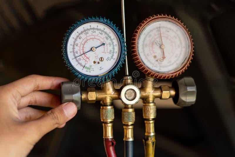 El retrato de una mano del mecánico utiliza un indicador de presión para conocer una función del dínamo foto de archivo