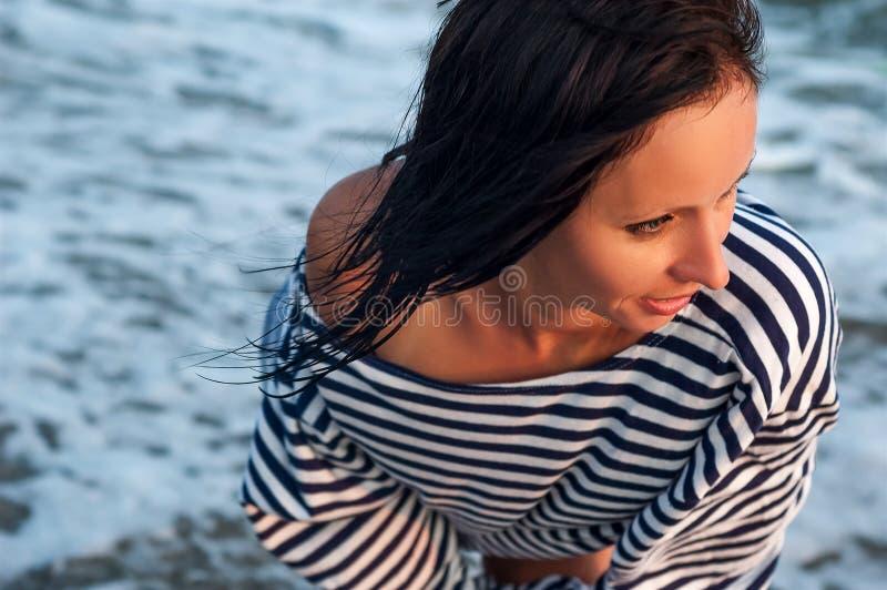 El retrato de una muchacha alegre en la puesta del sol en la playa, se relaja imagen de archivo libre de regalías