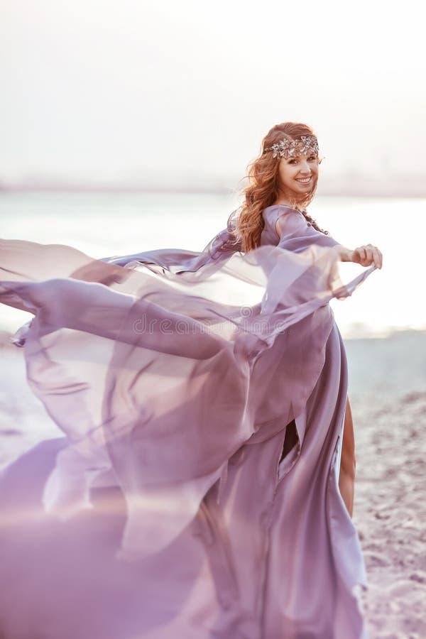 El retrato de una muchacha en un vestido de la luz de hadas está caminando imagen de archivo