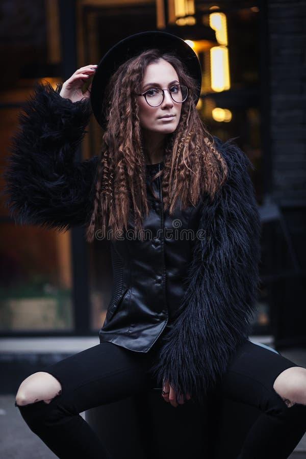 El retrato de una muchacha hermosa con marrón observa en vidrios en un sombrero negro y la capa con la piel se sienta en un barri fotos de archivo