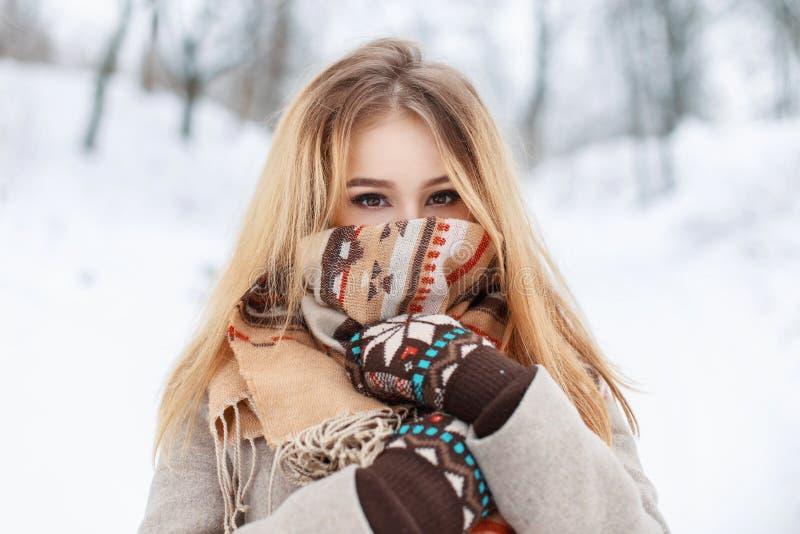 El retrato de una muchacha hermosa en una bufanda y los guantes en invierno equiparan imágenes de archivo libres de regalías