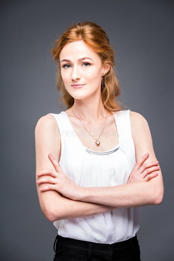 El retrato de una muchacha hermosa pelirroja joven en el estudio en un gris aisló el fondo Una mujer se está colocando con sus br foto de archivo