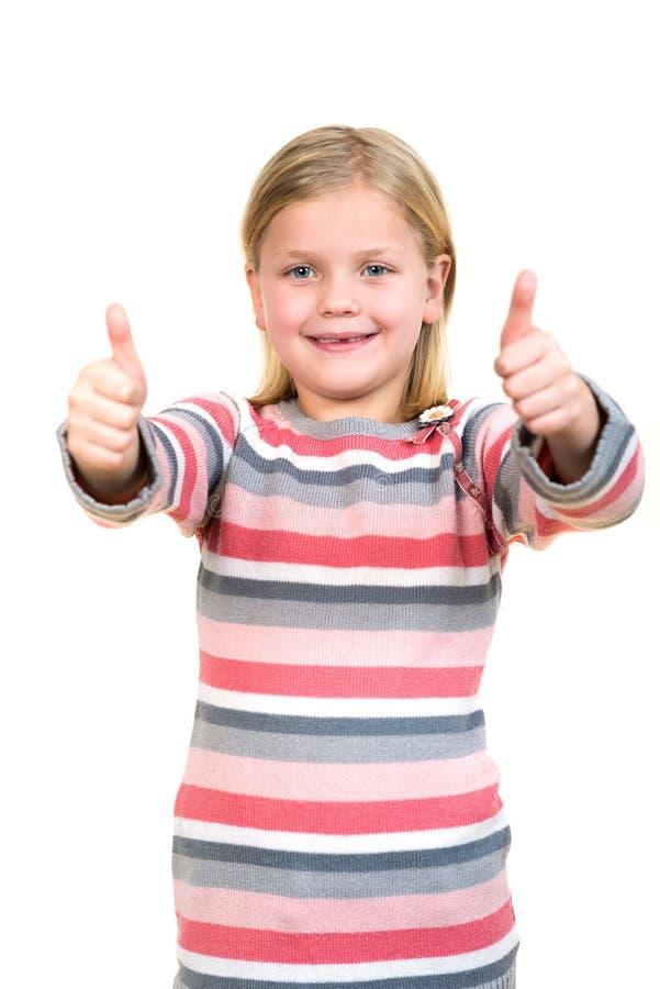 El retrato de una muchacha hermosa y confiada que mostraba los pulgares para arriba aisló un blanco foto de archivo libre de regalías