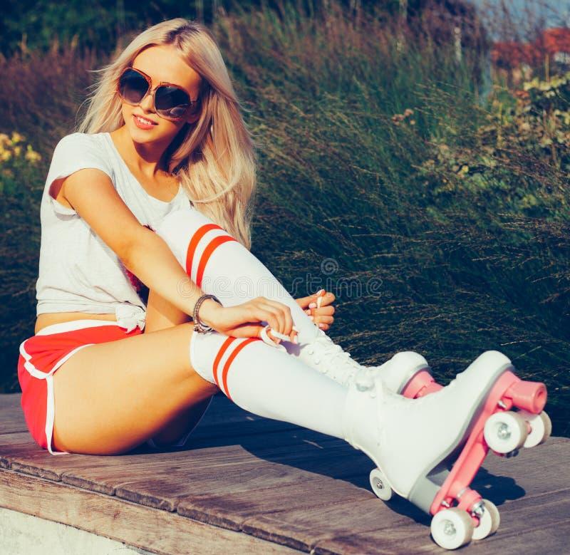 El retrato de una muchacha rubia joven hermosa aprieta los cordones que se sientan en un banco en los pcteres de ruedas del vinta imagenes de archivo