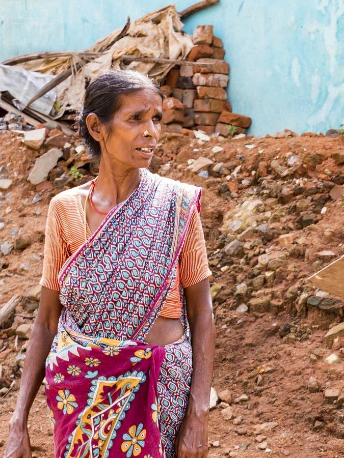 El retrato de una mujer asiática en el vestido nativo que mira en el lado, en pueblo pobre foto de archivo libre de regalías