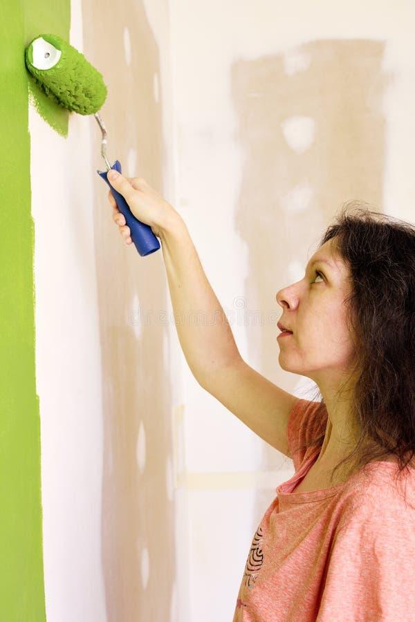 El retrato de una mujer bastante joven en camiseta rosada está pintando cuidadosamente la pared interior verde con el rodillo en fotografía de archivo