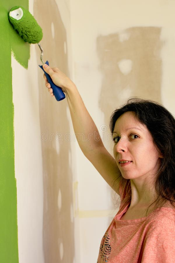El retrato de una mujer bastante joven en camiseta rosada está pintando la pared interior verde con el rodillo en un nuevo hogar imágenes de archivo libres de regalías