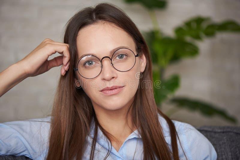 El retrato de una mujer bastante joven está llevando vidrios redondos fotografía de archivo libre de regalías