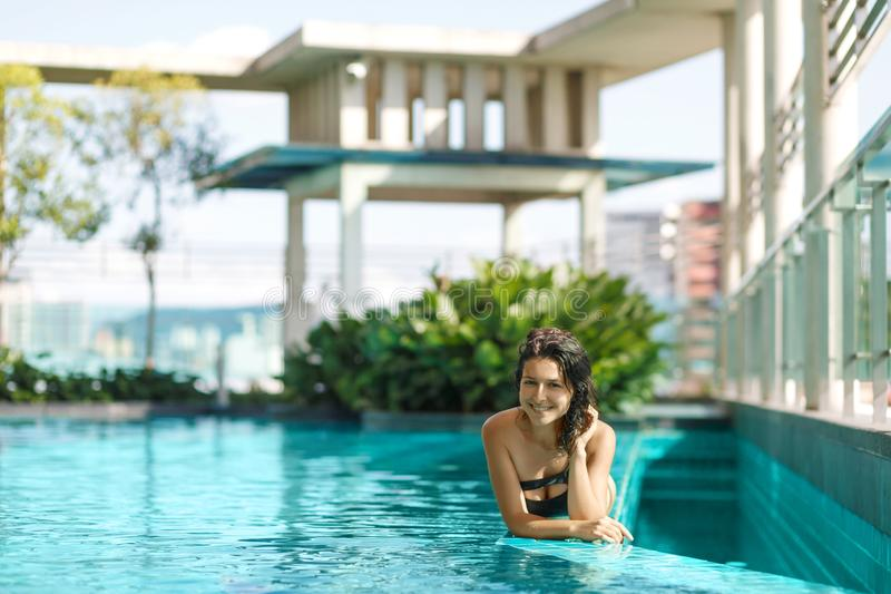 El retrato de una mujer cauc?sica sonriente atractiva en un traje de ba?o pone al borde de una piscina del tejado con los arbusto foto de archivo libre de regalías