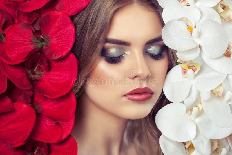 El retrato de una mujer con maquillaje hermoso sostiene una orquídea blanca y roja en sus manos fotos de archivo libres de regalías