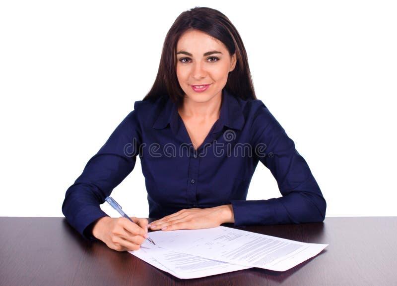 El retrato de una mujer de negocios alegre que se sienta en su escritorio Adan firma para arriba el contrato en el fondo blanco imagen de archivo