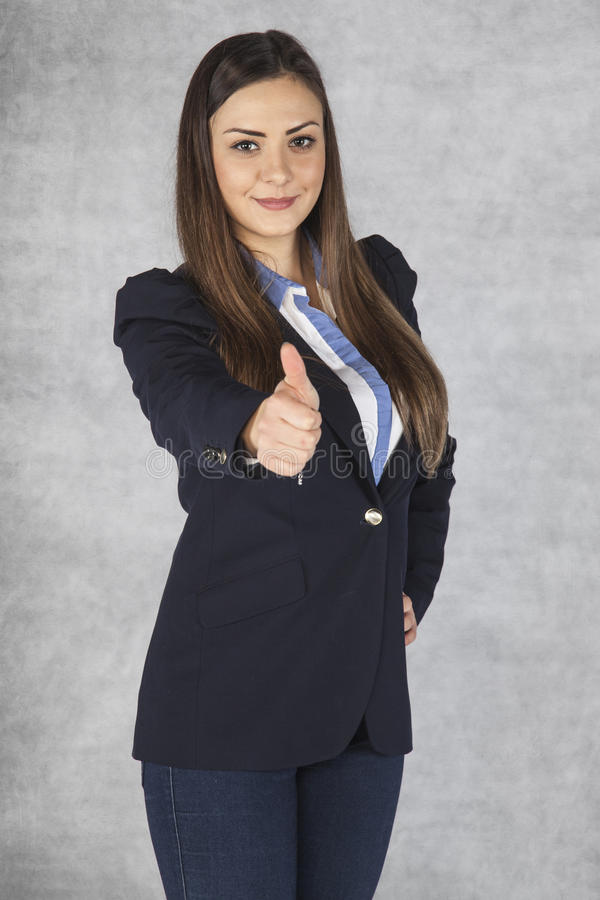 El retrato de una mujer de negocios joven hermosa con los pulgares sube el cele imagen de archivo
