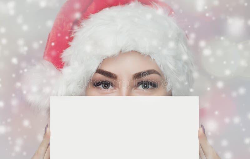 El retrato de una mujer hermosa en un sombrero rojo y un suéter rojo hecho punto de Santa Claus sostiene en su mano una hoja de p imagen de archivo libre de regalías
