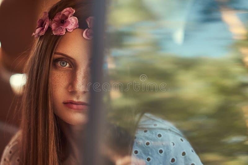 El retrato de una mujer hermosa en un vestido blanco y el blanco enrruellan en la cabeza, sentándose en el coche en el asiento tr imágenes de archivo libres de regalías