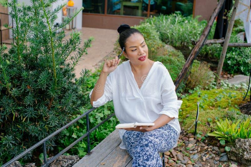 El retrato de una mujer hermosa que escribe en un libro está sentando el pensamiento en el trabajo en el parque fotografía de archivo libre de regalías