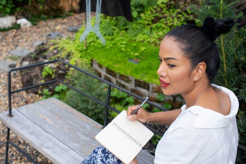 El retrato de una mujer hermosa que escribe en un libro está sentando el pensamiento en el trabajo en el parque foto de archivo